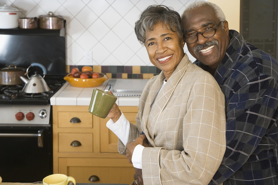 older African American couple hugging in kitchen