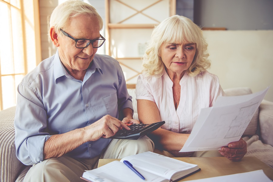 older man and woman examining documents using calculator CCRC financial viability