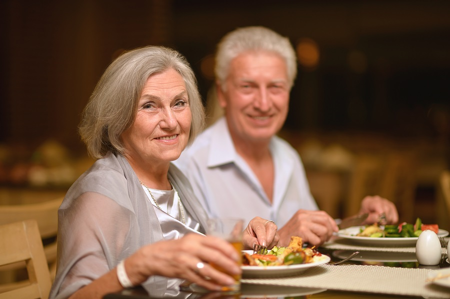 Happy mature couple eating dinner at restaurant meal plans at a CCRC