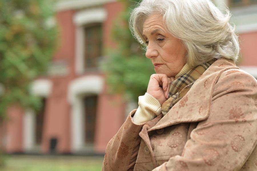 Portrait of a sad older woman in autumn park