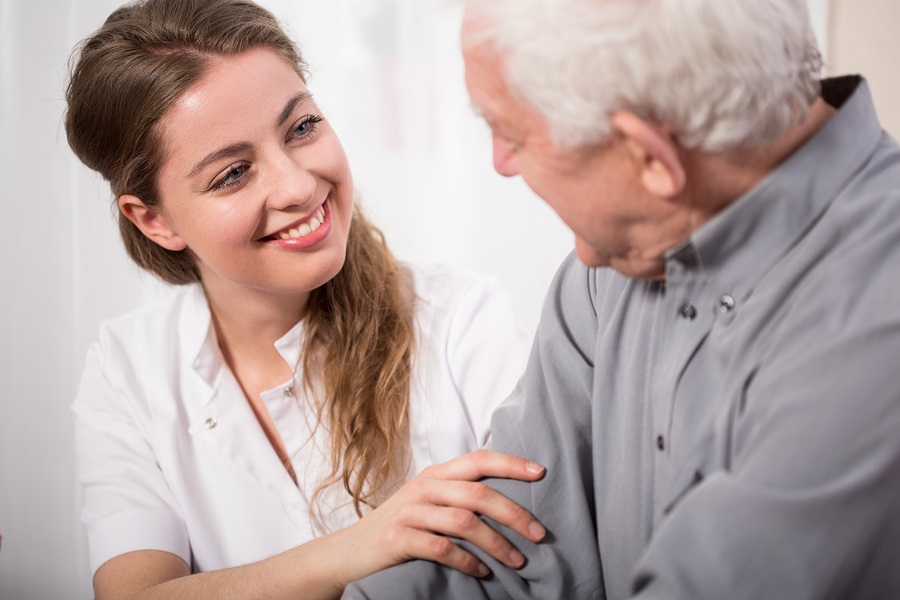 smiling nurse assisting senior man