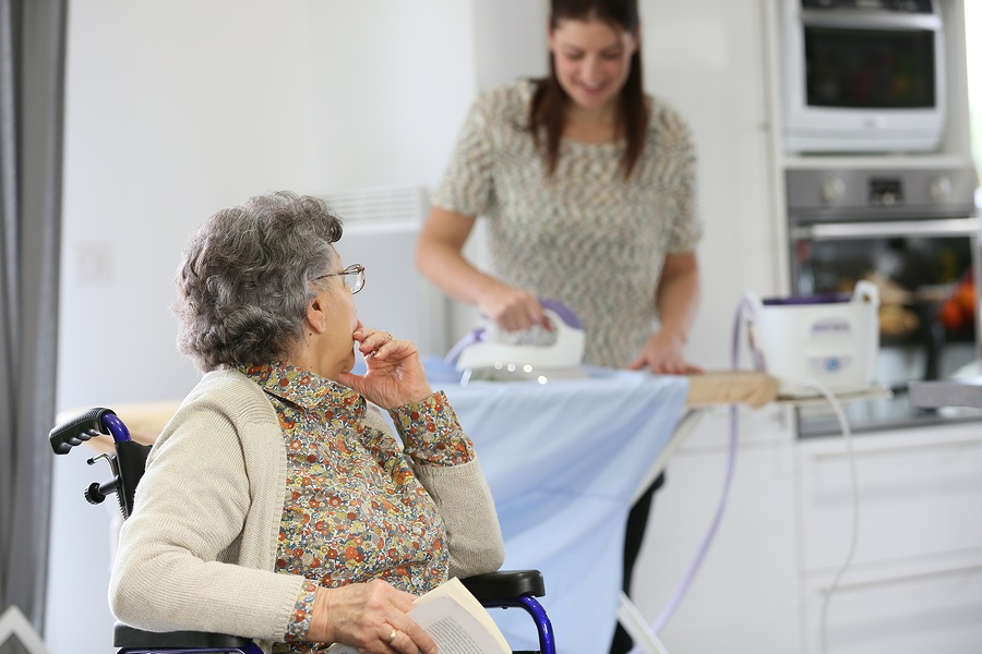 Elderly woman reading book while home helper irons laundry caregiver
