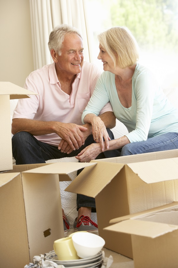 Senior Couple Moving Home And Packing Boxes