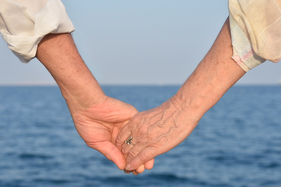 close up Elderly couple holding hands over sea background
