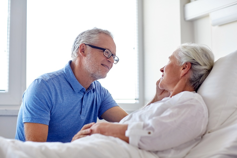 older man comforting an older woman in a hospital bed