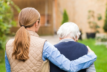Young woman walking with her arm around the back of an elderly woman caregiver assistance