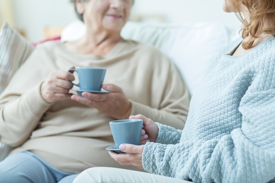 Two elderly women drinking coffee during conversation at home conversation with aging parent