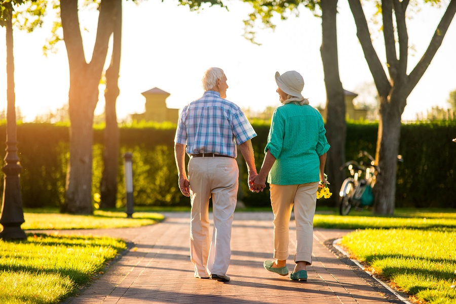 Back view of senior couple. People walking and holding hands. Do CCRC residents live longer