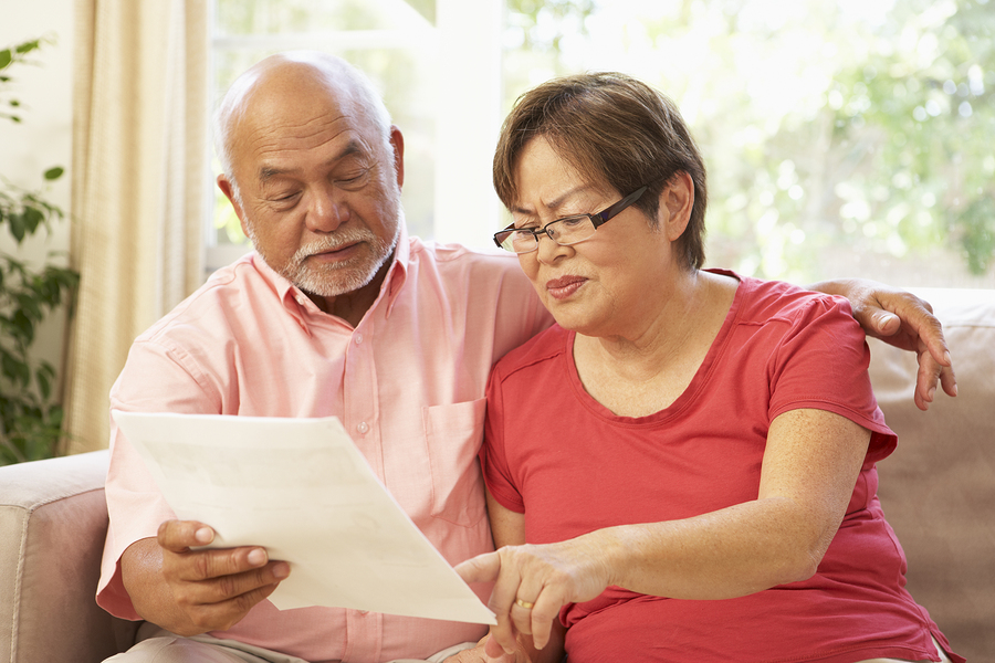 refundable CCRC entry fees Senior Couple Discussing Document At Home