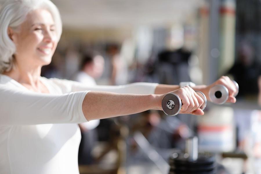 senior wellness health older woman weight training at a gym