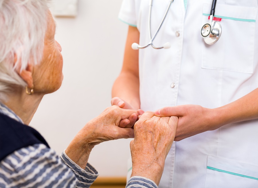 continuum of care nurse holding the hands of an older woman