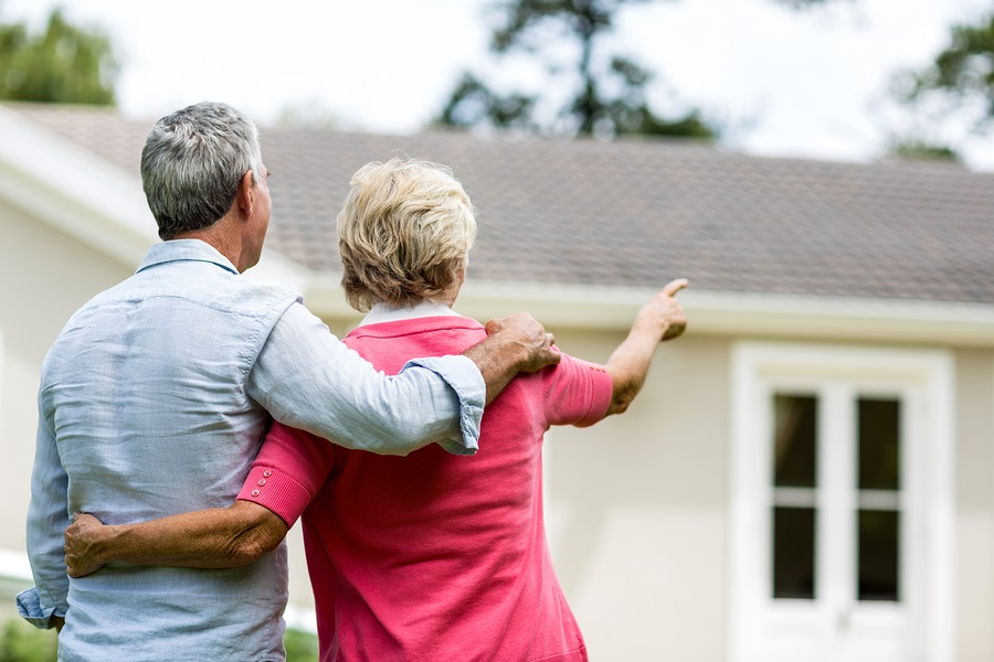 CCRC attracting younger residents older couple outside of their home
