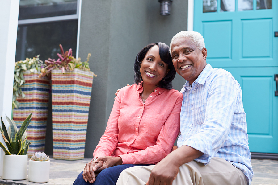 CCRC age requirements older couple sitting on outside house steps