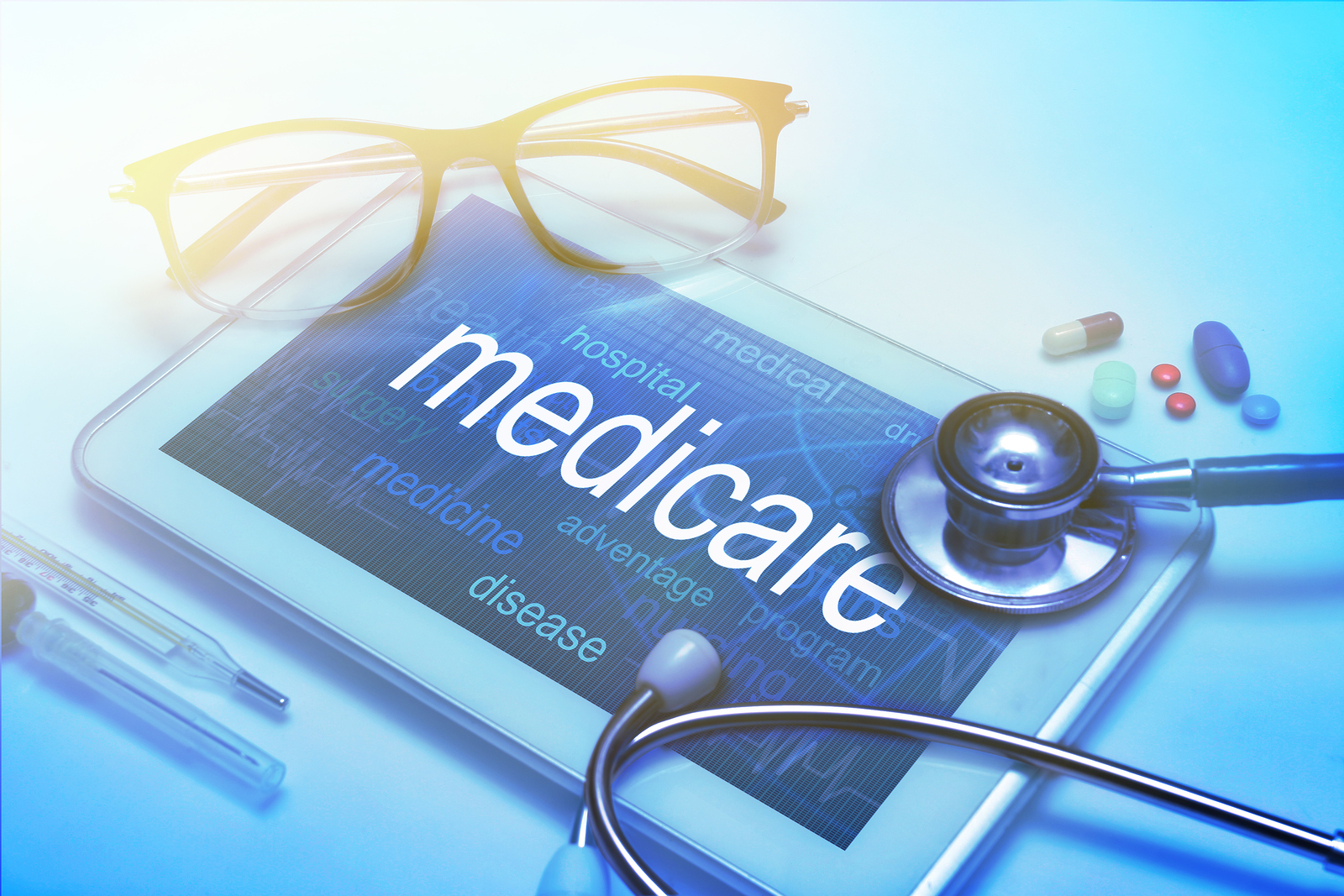 Medicare word on tablet screen with medical equipment on background