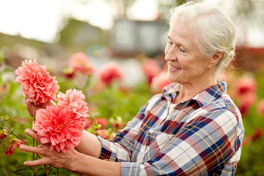 positive aging woman working in flower garden