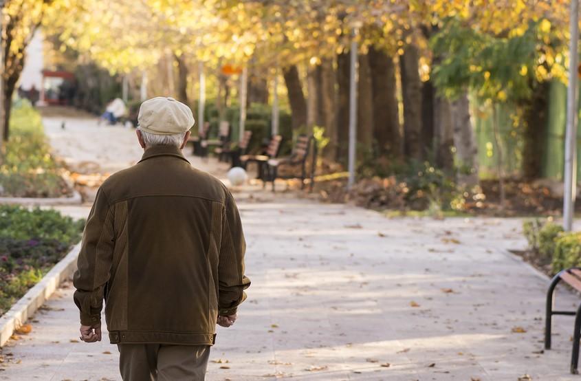 man walking alone down the sidewalk