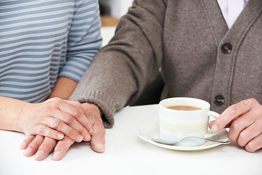 Woman Sharing Cup Of Tea With Elderly Parent