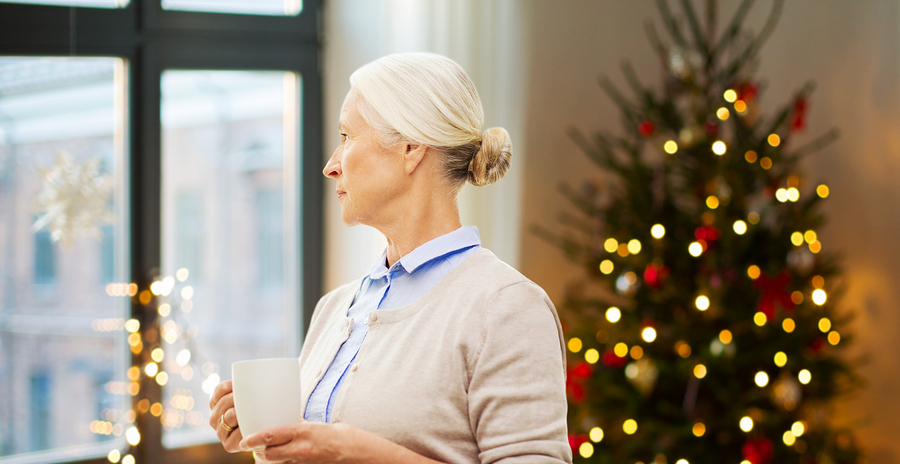 senior woman with cup of tea or coffee looking through window at home over christmas tree lights background