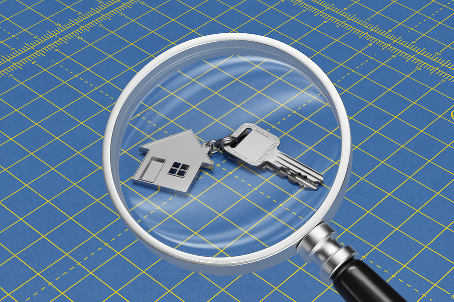 House and keys under magnifying glass as a home search concept