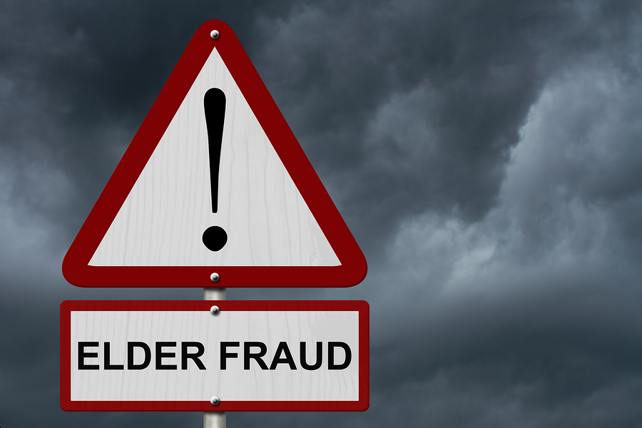 Elder Fraud Caution Sign Red and White Triangle Caution sign with word Elder Fraud with stormy sky background
