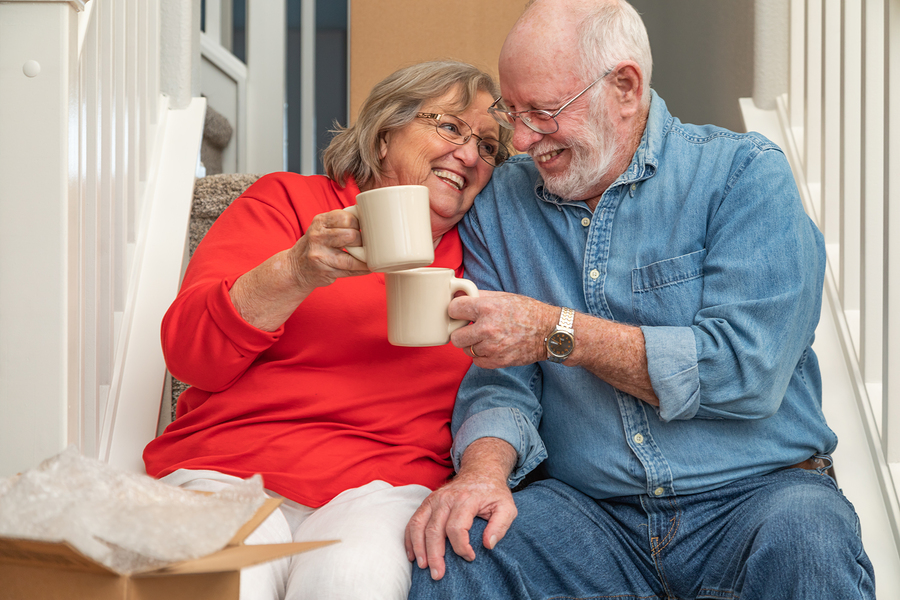 Senior Adult Couple Resting on Stairs with Cups of Coffee Surrounded with Moving Boxes