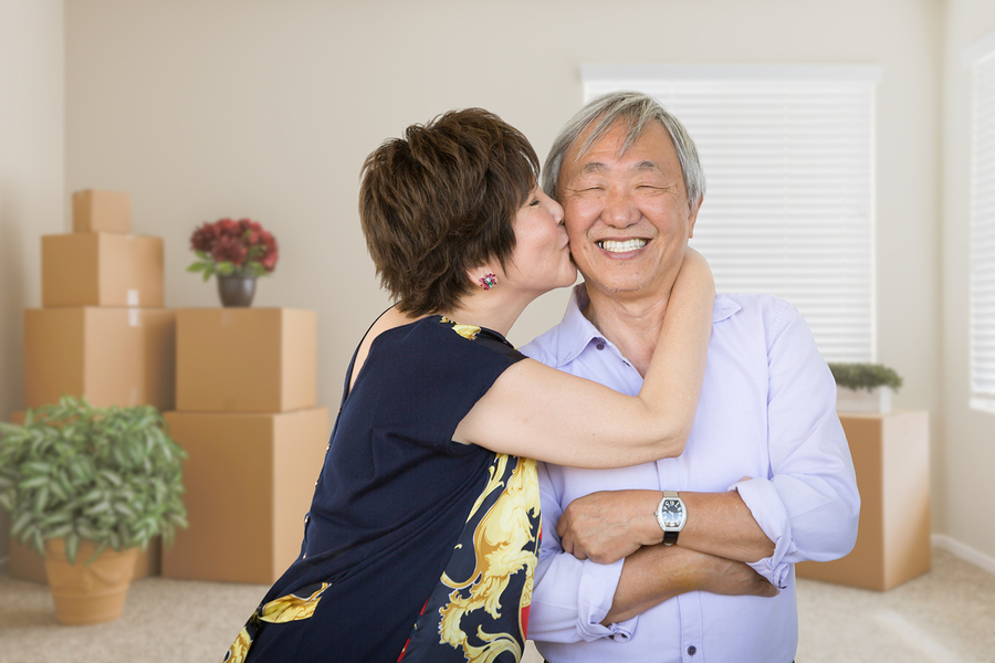 older Couple Inside Empty Room with Moving Boxes and Plants.