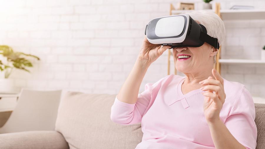 Senior Woman Wearing Virtual Reality Goggles At Home