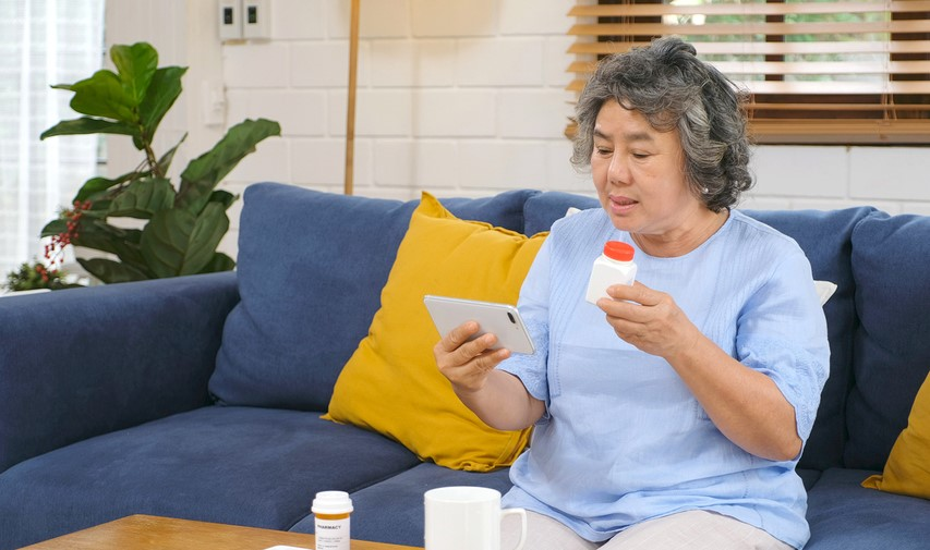 Senior woman holding bottle of pills and smartphone