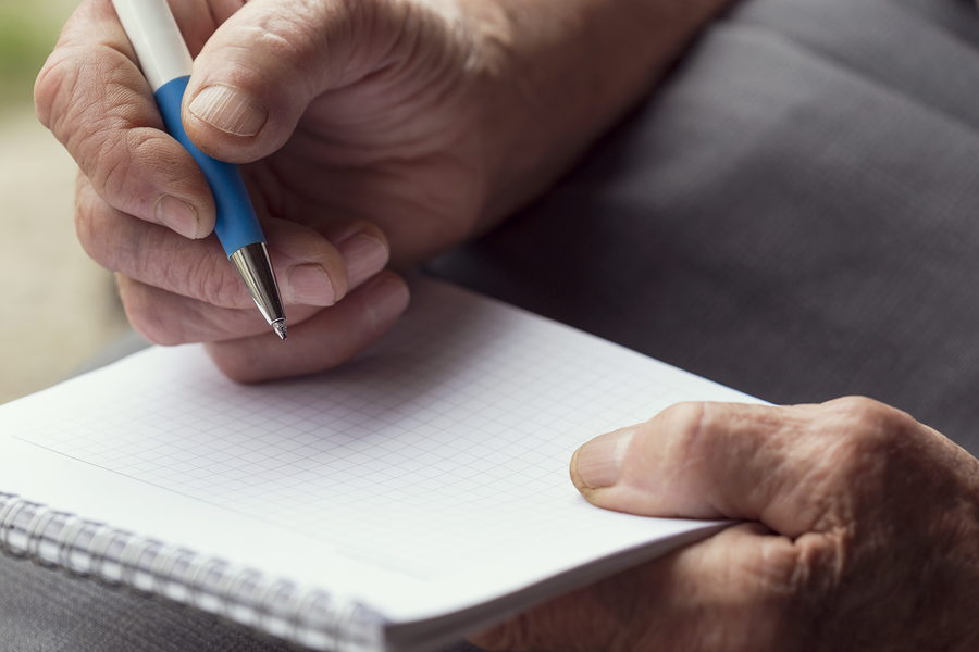 Prospective CCRC Resident Questions Detail of an elderly woman's hands holding a pen and writing a list