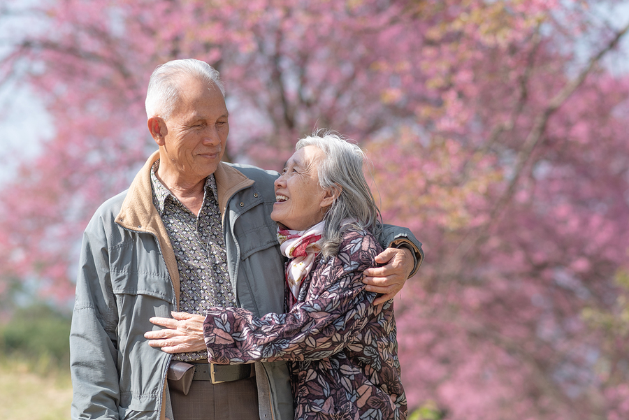 terminology ccrc lifecare lifeplan community Happy old couple smiling in a park.mature couple with cherry blossom tree
