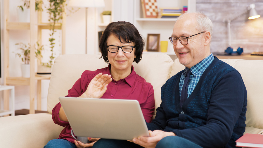 resiliency senior living Elderly Age Couple Sitting On Sofa Holding Laptop During A Video