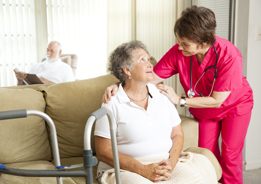 Senior woman at home with a caring nurse