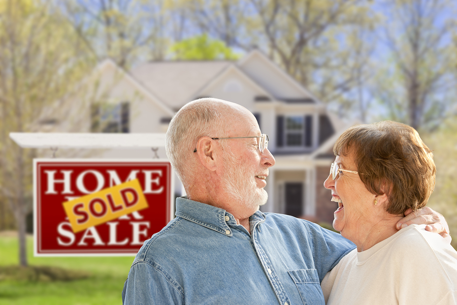 real estate market; couple with home sold sign