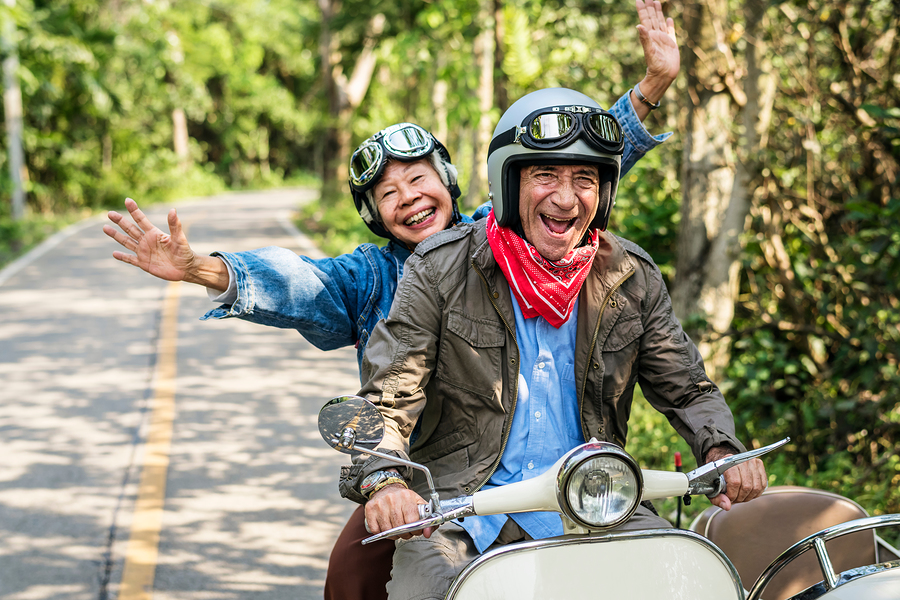 Senior couple riding a scooter; not ready yet for CCRC