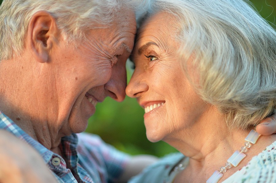 senior couple hugging in the summer park; aging dating