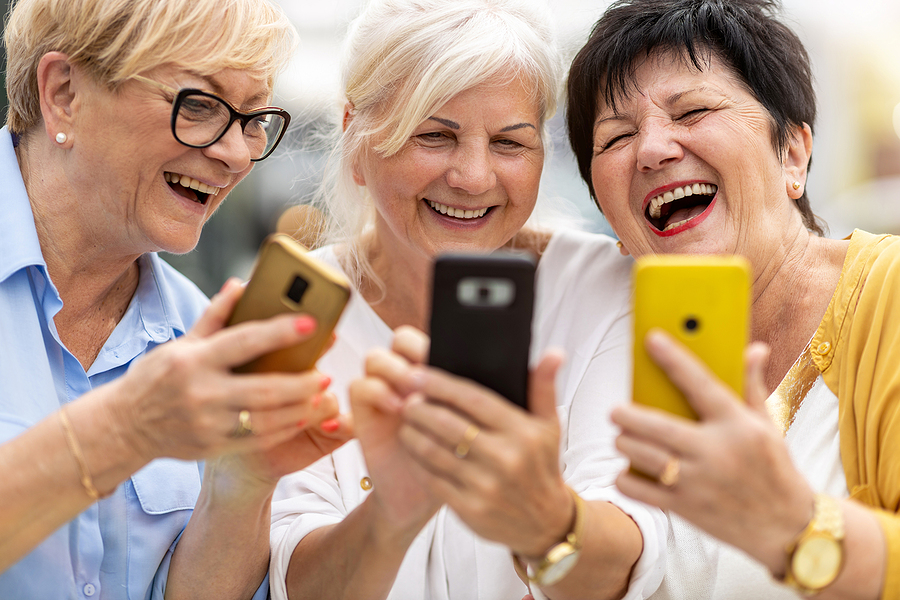 CCRC health benefits Group of senior women using smartphones together