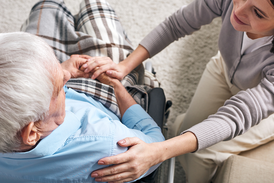 female caregiver sitting by senior man in wheelchair caregiver guilt