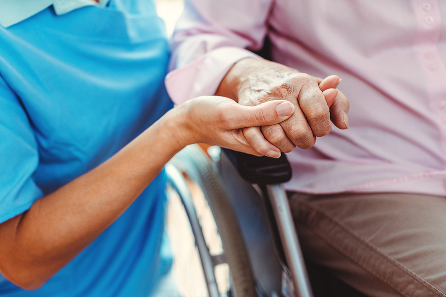 long-term care crisis Nurse consoling a senior woman in the nursing home holding her hand in the nursing home