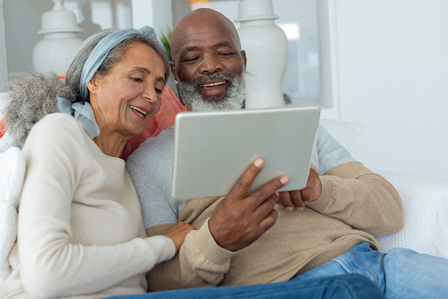 Front view of diverse senior couple using a digital tablet rental retirement community