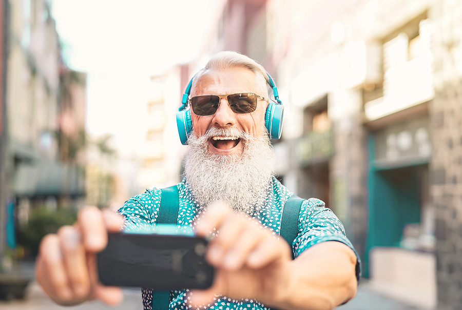 Senior bearded man taking selfie with mobile phone while listening favorite playlist with headphones younger seniors subjective age