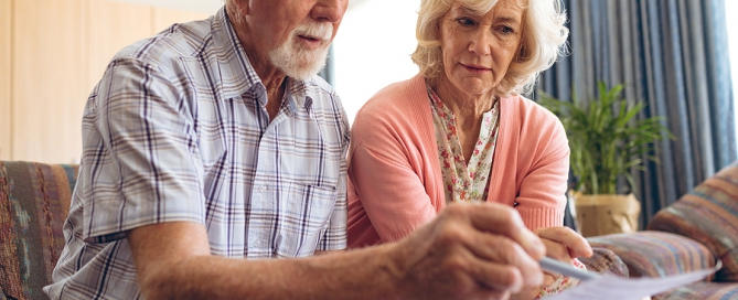 senior couple looking at bill cost of senior living community