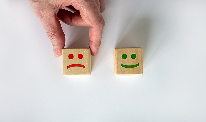 life plan community management customer satisfaction; Close Up Hand Choose Smiley Face Icon On Wood Cube