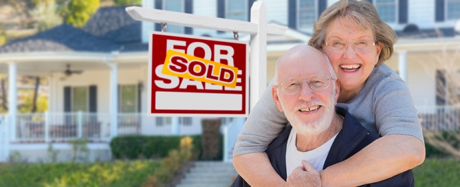 Senior Adult Couple in Front of Sold Home For Sale sign; selling your home