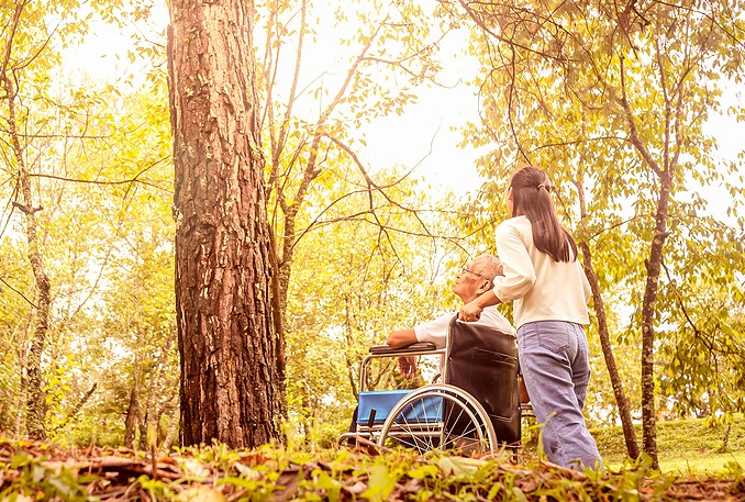 elderly man in wheelchair being pushed by woman; cost of family caregiving