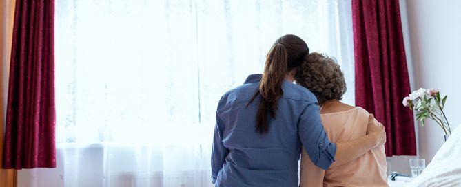 dementia caregiving; woman hugging elderly woman by window