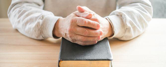 retired clergy housing allowance senior man praying with bible