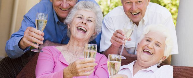 Two senior Couples On Patio Drinking Champagne And Smiling; CCRC age