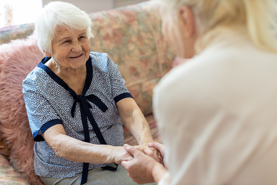 Female caregiver supporting old woman to stand up from the sofa family caregiving stress