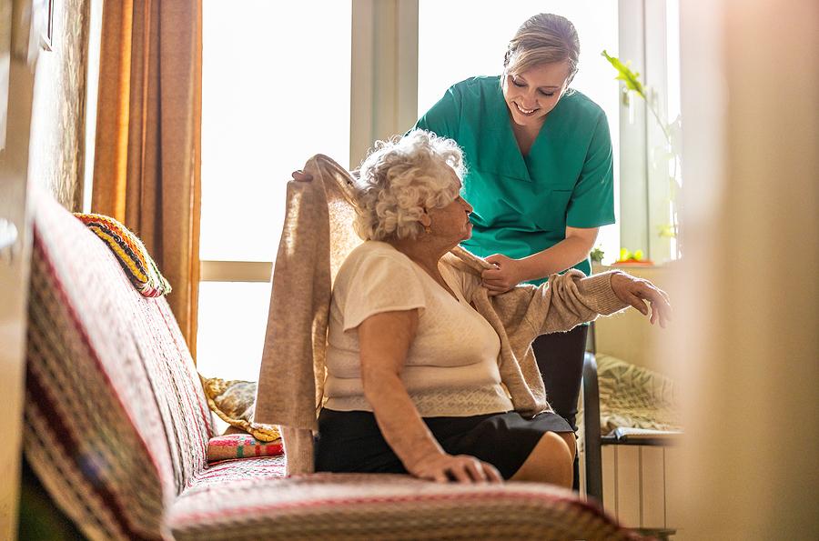 Female nurse taking care of a senior woman at home health care