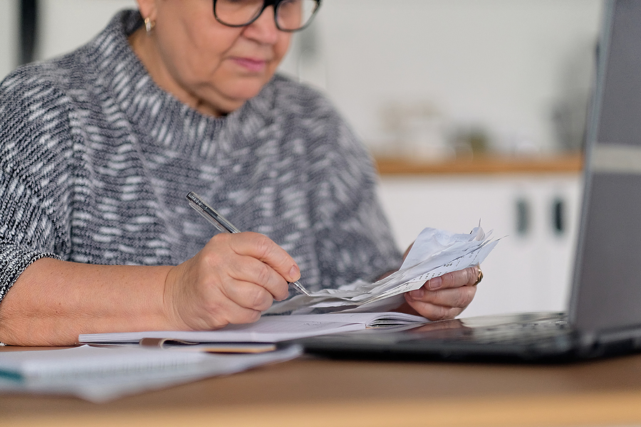 planning financially for CCRC move; woman with papers and calculator